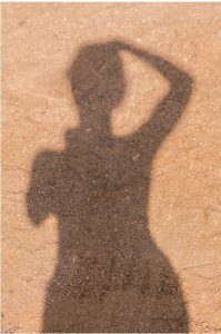 Varjokuva hiekalla naisvartalosta